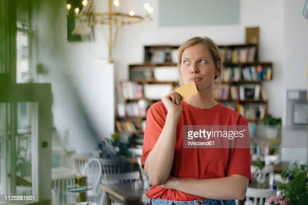 young woman holding card in a cafe thinking - uncertainty stock pictures, royalty-free photos & images