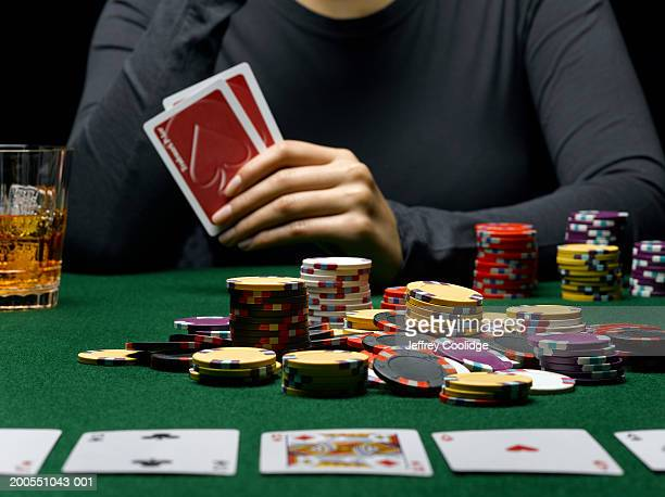 young woman holding cards at poker table, mid section - ポーカー ストックフォトと画像