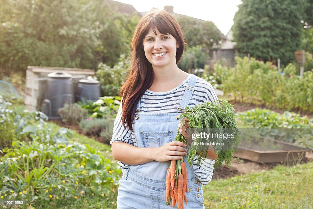 Young woman holding carrots at allotment : Stock Photo