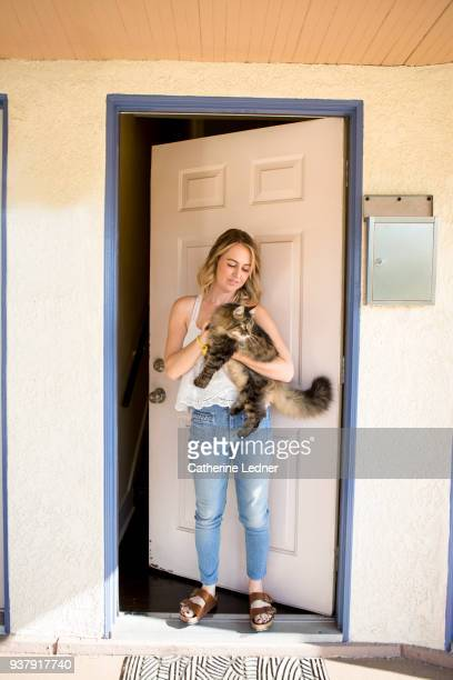 Young woman holding cat in doorway.