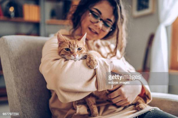 young woman holding cat - cat family stock pictures, royalty-free photos & images
