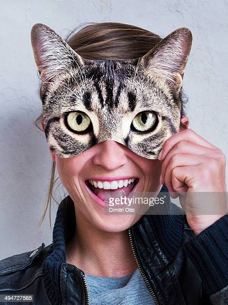 Young woman holding cats eyes mask over her eyes