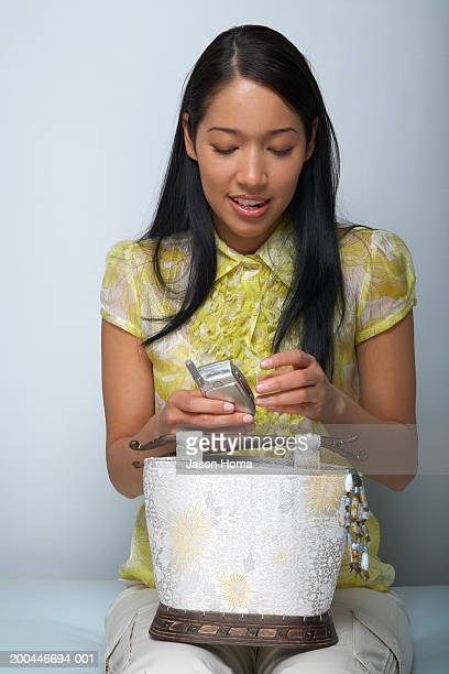 young woman holding cell phone, close-up - long purse stock photos and pictures