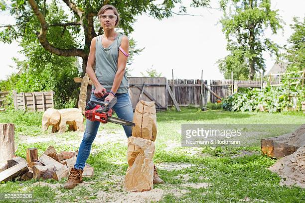 Young woman holding chainsaw, portrait