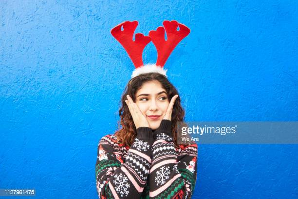 young woman holding cheeks and wearing festive antlers - sloppy joe, jr stock pictures, royalty-free photos & images