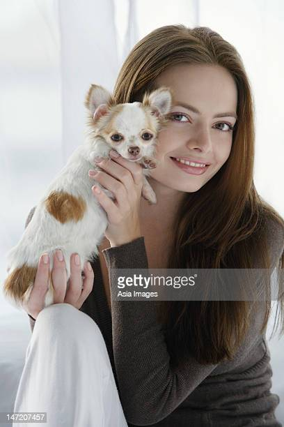 Young woman holding chihuahua