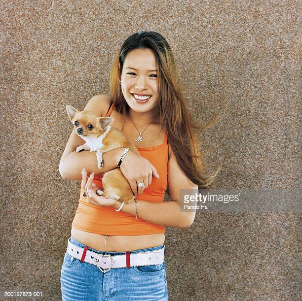 Young woman holding chihuahua, smiling, portrait