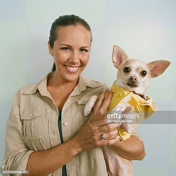 Young woman holding Chihuahua wearing raincoat, smiling, portrait