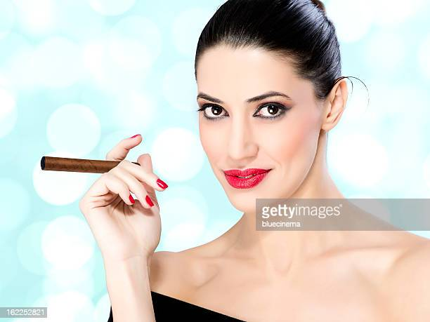 young woman holding cigar - beautiful women smoking cigarettes stock photos and pictures
