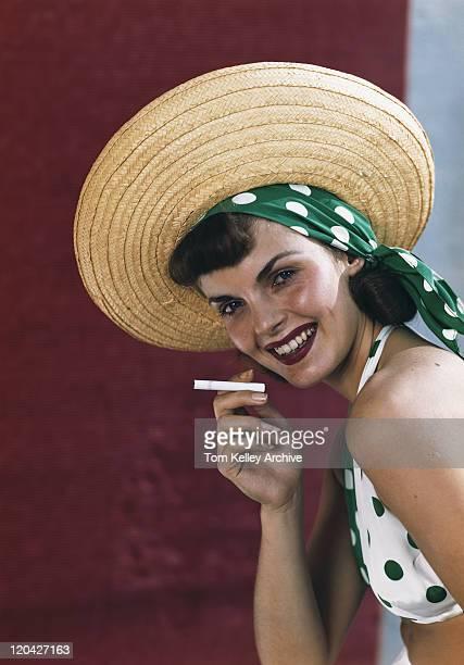 Jeune femme tenant une cigarette et souriant, portrait