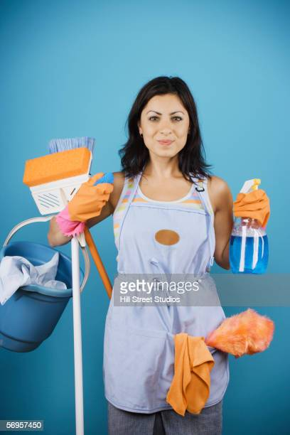 Young woman holding cleaning supplies