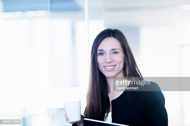 young woman holding coffee cup and ring binder file looking at camera smiling - sigrid gombert photos et images de collection