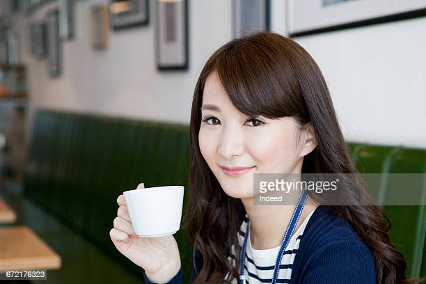 Young woman holding coffee cup at restaurant