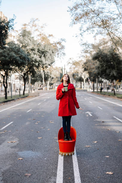 Young woman holding coffee cup day dreaming while standing on seat at street