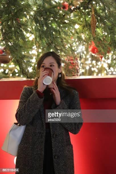 若い女性のコーヒーカップを手