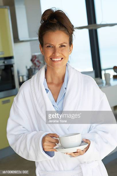 Young woman holding coffee cup, smiling, portrait