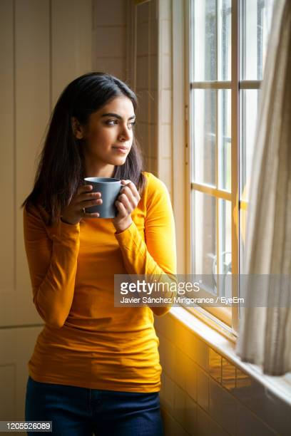 young woman holding coffee cup standing by window at home - one young woman only stock pictures, royalty-free photos & images