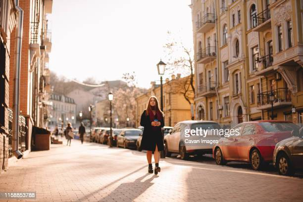 young woman holding coffee cup while walking on street - キエフ市 ストックフォトと画像