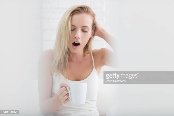 Young woman holding coffee cup, yawning