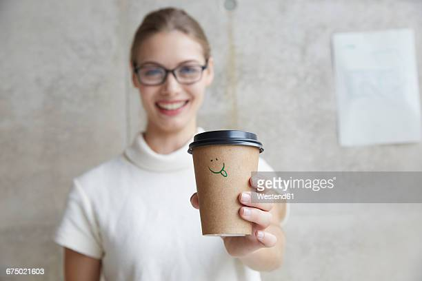 Young woman holding coffee to go cup with smiley face on it
