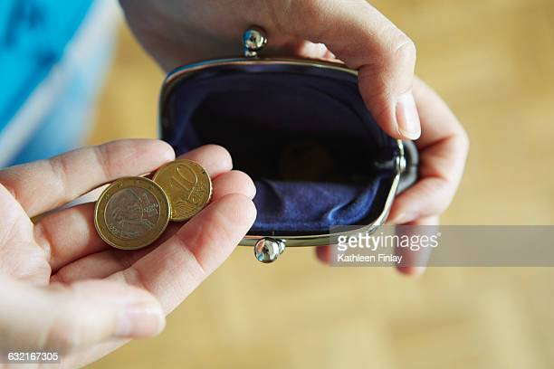 Young woman holding coins from purse, close-up
