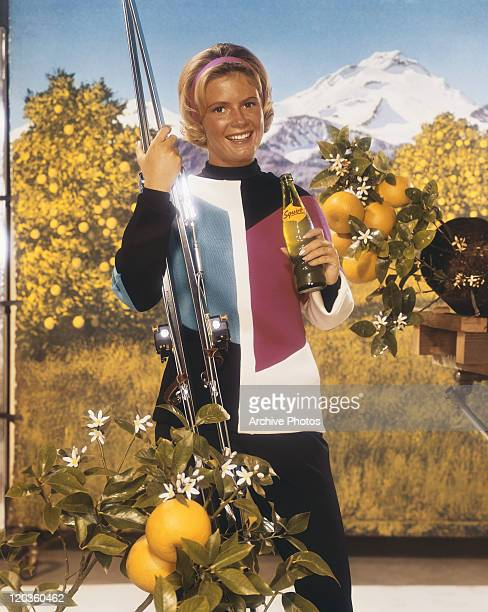 Young woman holding cold drink and ski, smiling, portrait
