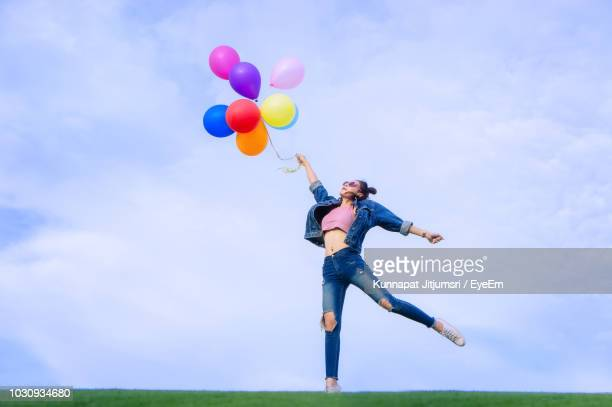 young woman holding colorful balloons while standing against sky - helium balloon stock pictures, royalty-free photos & images