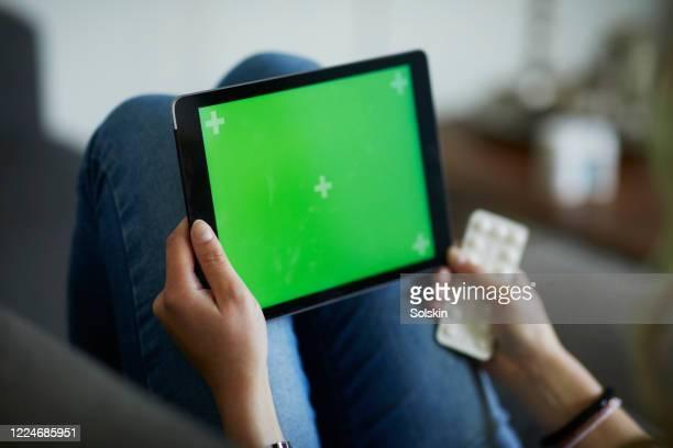 young woman holding computer tablet with green screen, medicine in hands - selandia fotografías e imágenes de stock