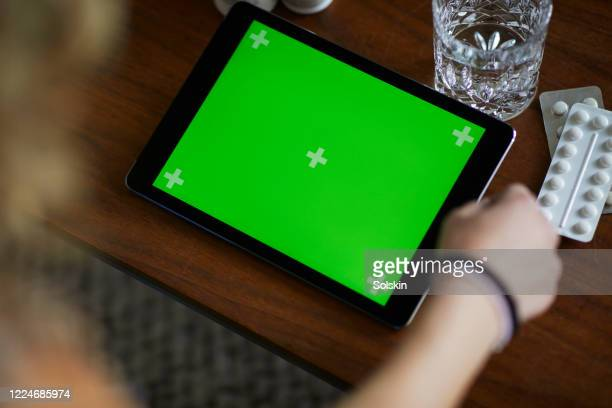 young woman holding computer tablet with green screen, medicine in hands - chroma key foto e immagini stock