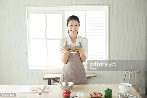 Young woman holding cookie plate by table