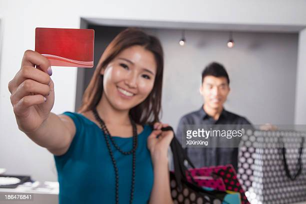 Young woman holding credit card at fashion store