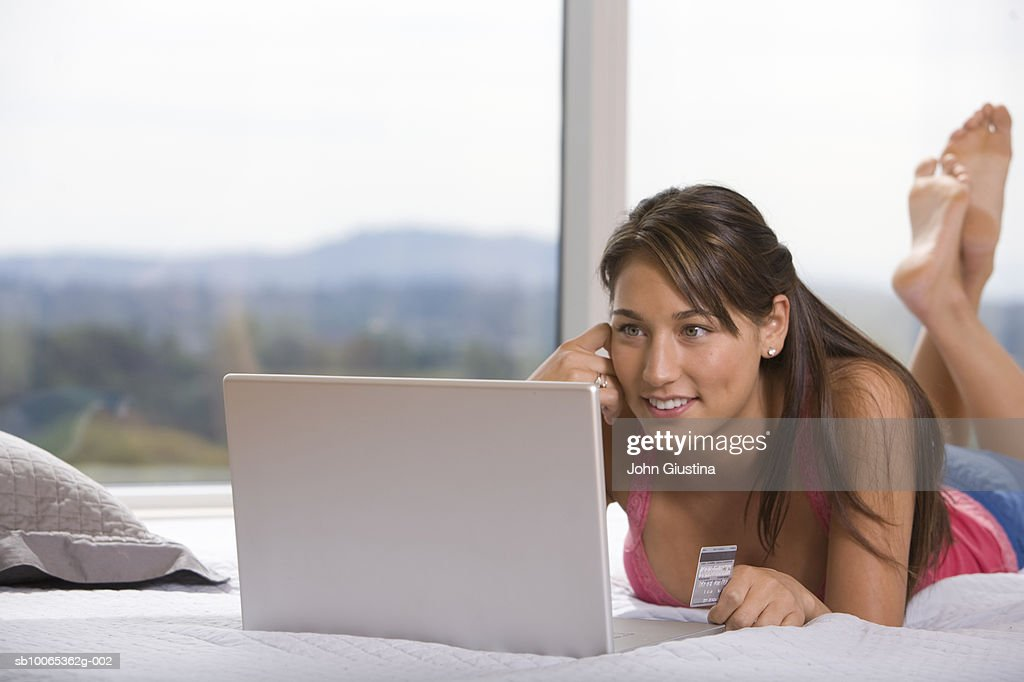 Young woman holding credit card  lying on bed using laptop : Foto stock