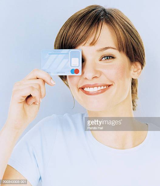 Young woman holding credit card over one eye, smiling, close-up