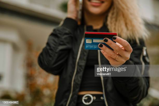 young woman holding credit card - black nail polish stock pictures, royalty-free photos & images
