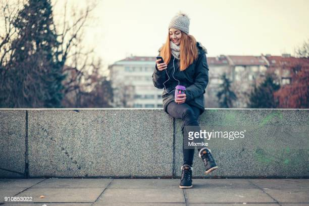 Young woman holding cup of coffee and chatting on her phone