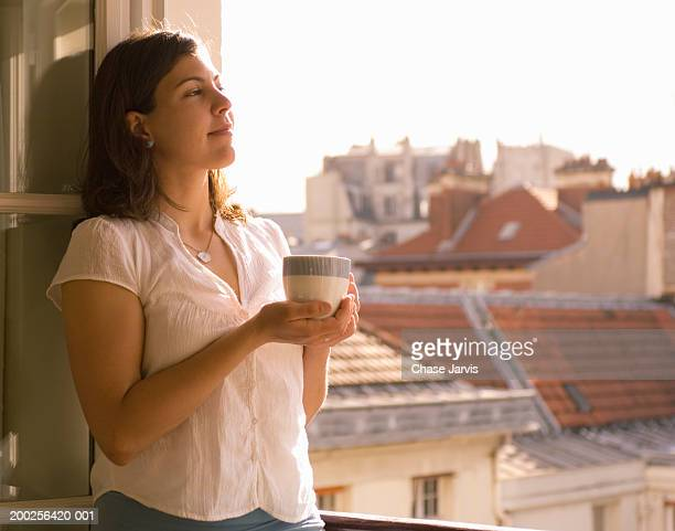young woman holding cup of coffee, looking out open window, side view - open blouse stock photos and pictures