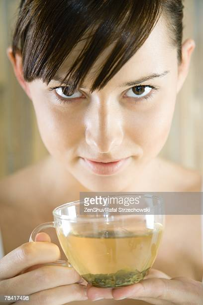 Young woman holding cup of herbal tea, looking at camera, close-up