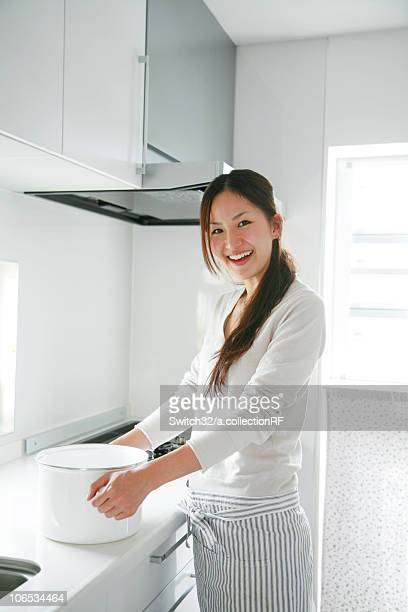 Young Woman Holding Deep Pan in Kitchen