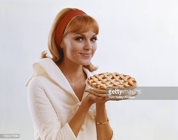 Young woman holding dessert pie against white background, portrait