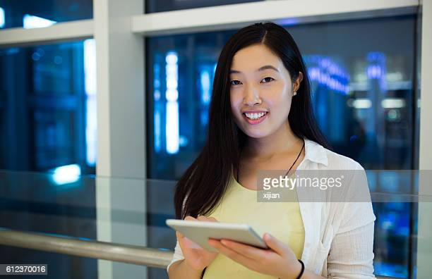 Young woman holding digital tablet at night