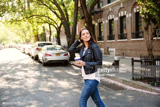 Young woman holding disposable cup while crossing city street