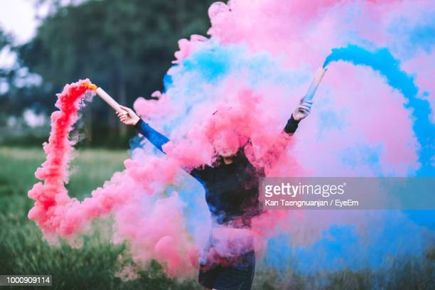 young woman holding distress flare on field - freezing motion photos stock pictures, royalty-free photos & images