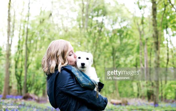 Young woman holding dog in woodland area