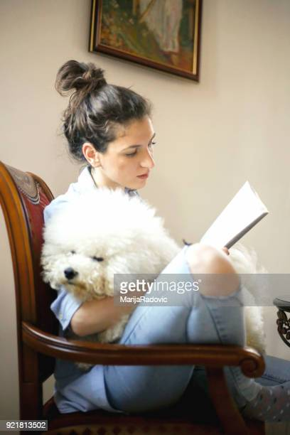 Young woman holding dog relaxing in her living room and reading book