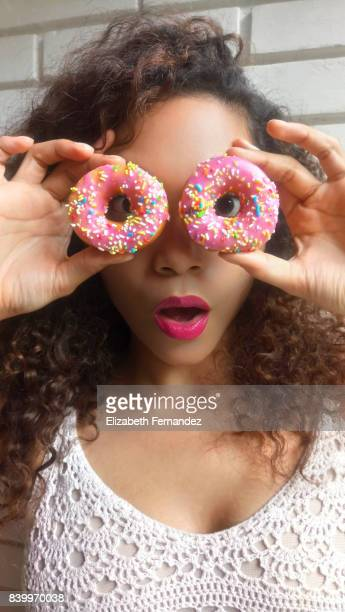 Young woman holding donuts up in front of her eyes