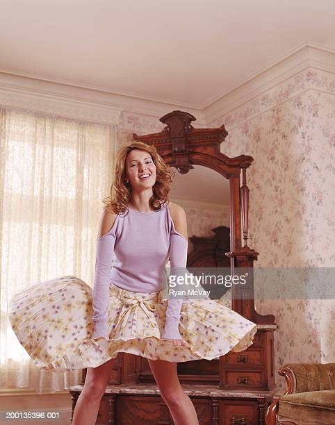 young woman holding down billowing skirt, indoors, smiling, portrait - wind blows up skirt stock pictures, royalty-free photos & images