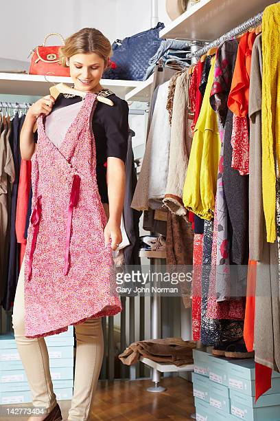 young woman holding dress against body in boutique