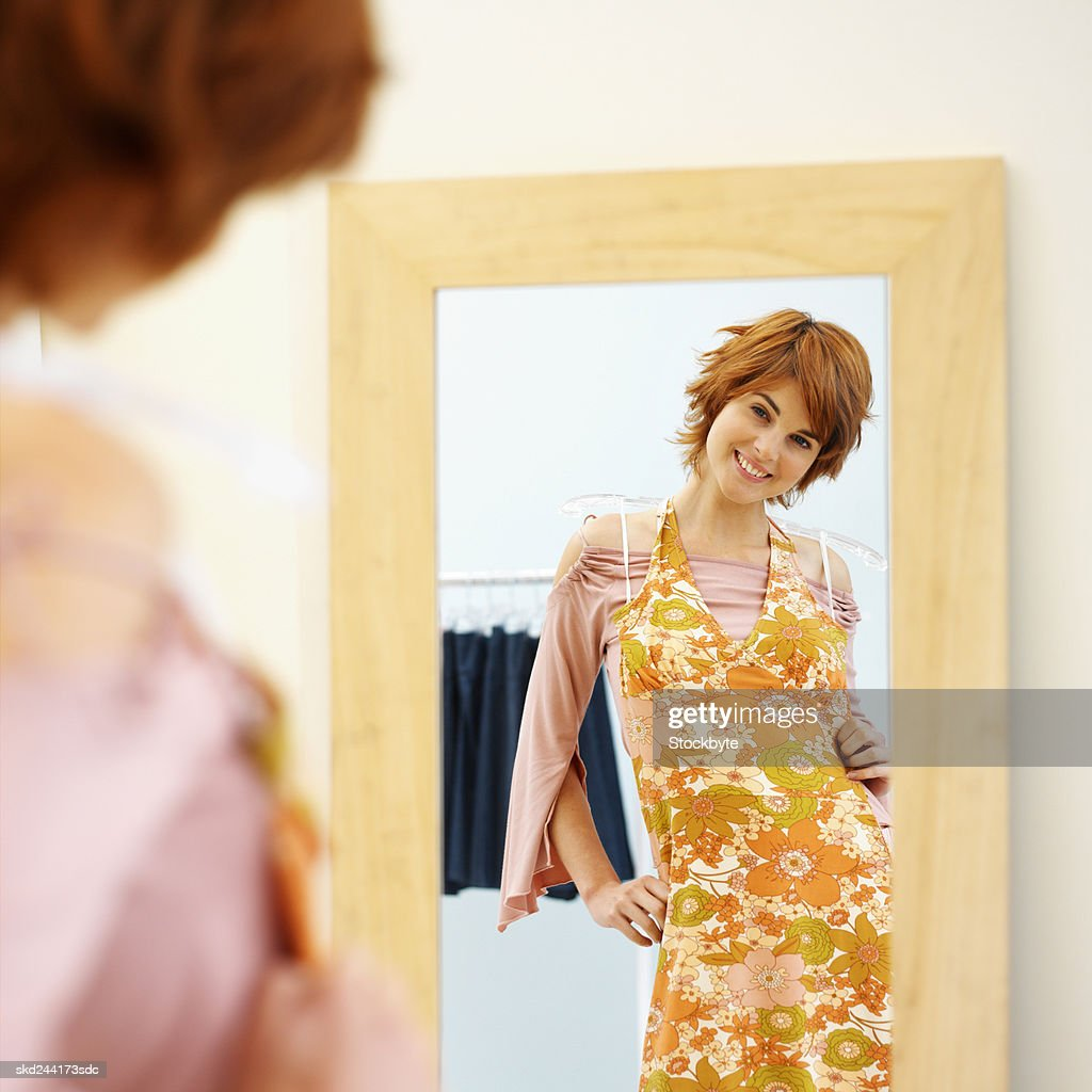 Young woman holding dress and looking in mirror : Stock Photo