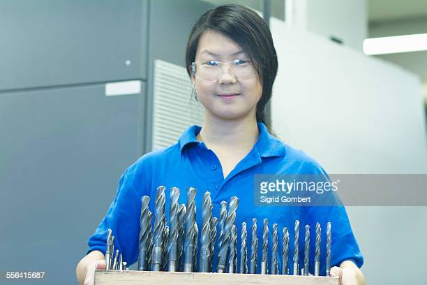 young woman holding drill bits - sigrid gombert photos et images de collection