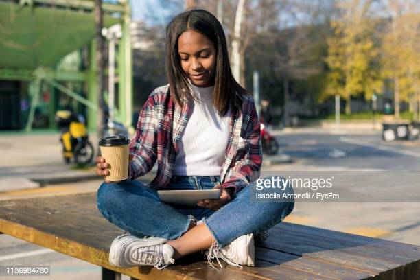 young woman holding drink and using digital tablet while sitting on wooden table outdoors - piernas cruzadas fotografías e imágenes de stock